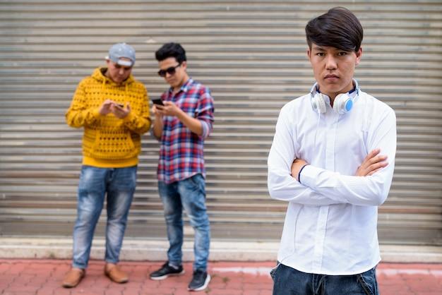 Portret van drie jonge aziatische mannen permanent tegen magazijn deur in de straten van bangkok, thailand