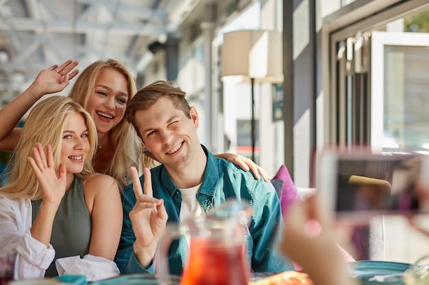 Portret van drie jonge beste vrienden zitten in café, foto nemen