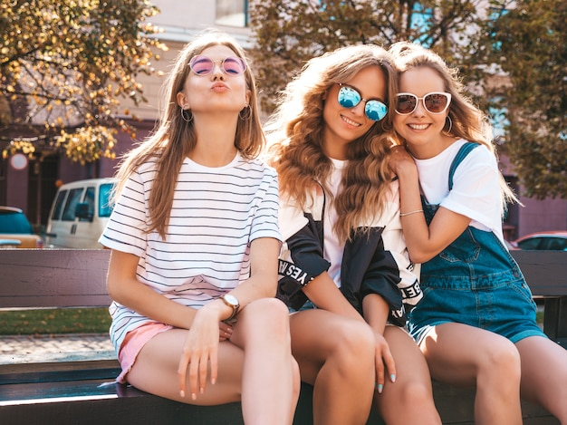 Portret van drie jonge mooie glimlachende hipster meisjes in trendy zomerkleren. sexy zorgeloze vrouwen die zich voordeed op straat. positieve modellen met plezier in een zonnebril