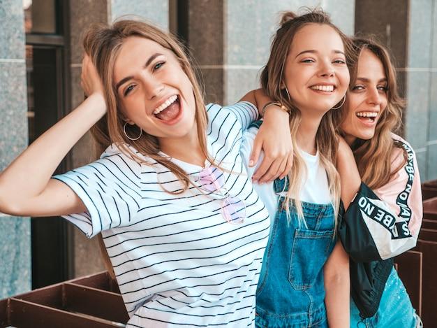Portret van drie jonge mooie glimlachende hipster meisjes in trendy zomerkleren. sexy zorgeloze vrouwen die zich voordeed op straat. positieve modellen met plezier