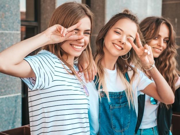 Portret van drie jonge mooie glimlachende hipster meisjes in trendy zomerkleren. sexy zorgeloze vrouwen die zich voordeed op straat. positieve modellen tonen vredesteken