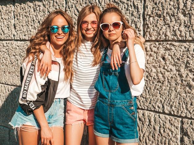 Portret van drie jonge mooie glimlachende hipster meisjes in trendy zomerkleren. sexy zorgeloze vrouwen poseren in de straat in de buurt van de muur. positieve modellen plezier in zonnebril