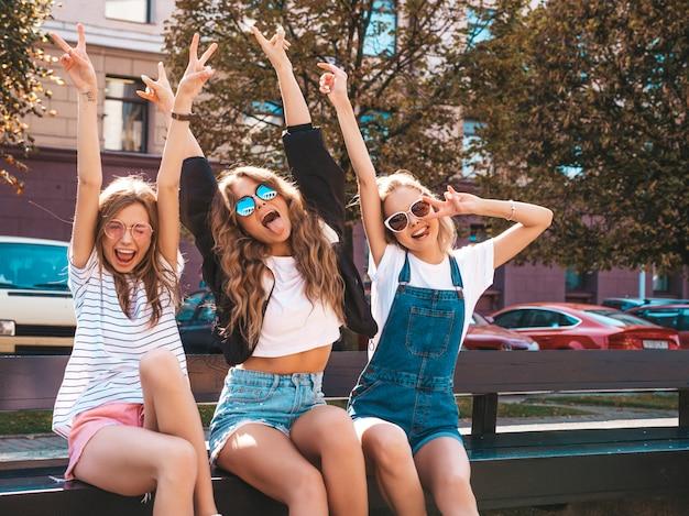 Portret van drie jonge mooie lachende hipster meisjes in trendy zomerkleding. sexy zorgeloze vrouwen zitten op de bank in de straat. positieve modellen plezier in zonnebril. het opheffen van handen