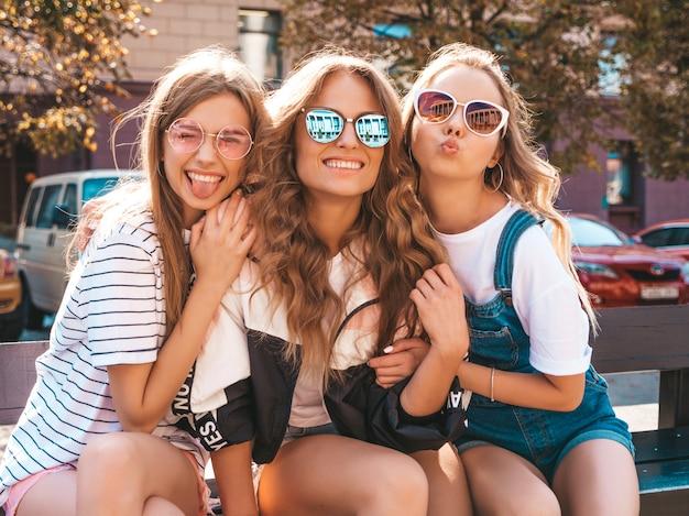 Portret van drie jonge mooie lachende hipster meisjes in trendy zomerkleding. sexy zorgeloze vrouwen zitten op de bank in de straat. positieve modellen plezier in zonnebril