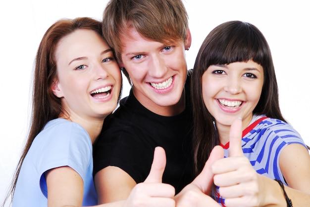 Portret van drie jonge tieners die en het thumbs-up-teken lachen geven.