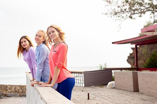 Portret van drie jonge vrouwelijke vrienden die dichtbij overzees lopen