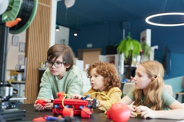 Portret van drie kinderen die robots bedienen tijdens de techniekles op de moderne school, kopieer ruimte