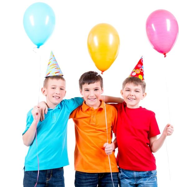 Portret van drie kleine jongens met gekleurde ballonnen en feestmuts - geïsoleerd op een witte