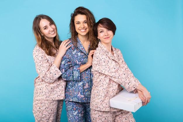 Portret van drie mooie jonge meisjes die kleurrijke pyjama's dragen die pret hebben tijdens sleepover die over blauwe achtergrond wordt geïsoleerd. pyjamafeest en vrijgezellenfeest concept