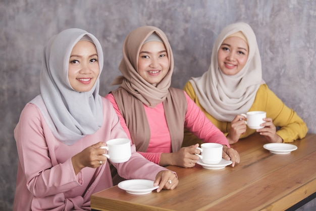 Portret van drie mooie moslimvrouw die samen een koffietijd hebben
