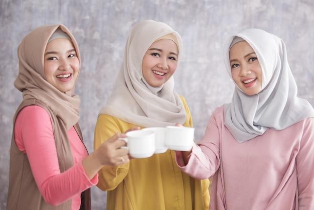 Portret van drie mooie moslimvrouwen proost op hun koffie voor een gelukkig leven