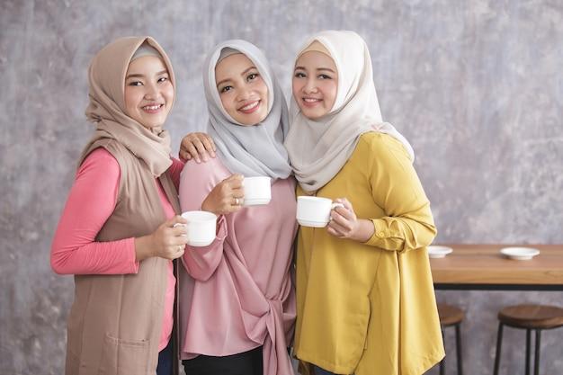 Portret van drie mooie moslimvrouwen staan en glimlachen terwijl kopjes koffie