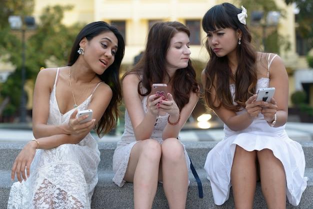 Portret van drie multi-etnische jonge mooie vrouwen als vrienden samen in het park buiten