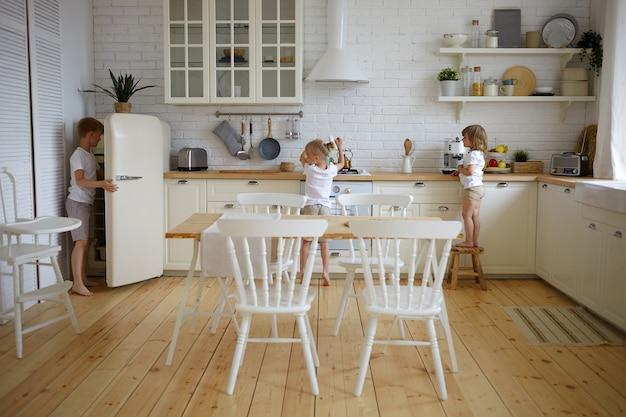 Portret van drie onafhankelijke kinderen, broers en zussen die zelf het avondeten bereiden terwijl de ouders aan het werk zijn. kinderen maken samen ontbijt in de keuken. voedsel, culinair, keuken, kindertijd en voedingsconcept