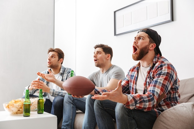 Portret van drie opgewonden jonge mannen kijken naar amerikaans voetbal terwijl ze thuis zitten met bier en snacks binnenshuis