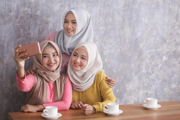 Portret van drie prachtige broers en zussen die selfies samen nemen in café met kopie ruimte