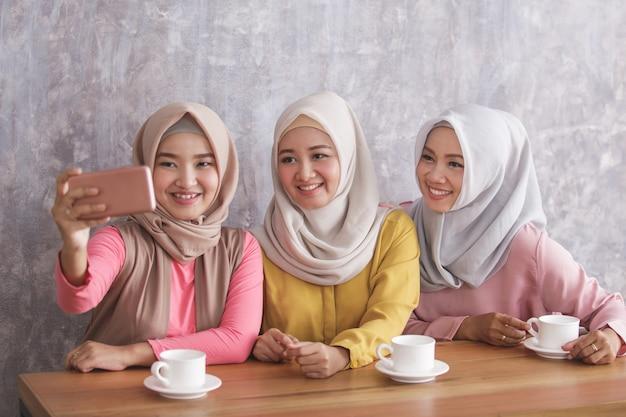 Portret van drie prachtige broers en zussen die selfies samen nemen in café