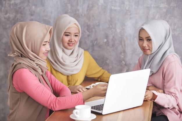 Portret van drie prachtige broers en zussen praten over hun nieuwe project in café