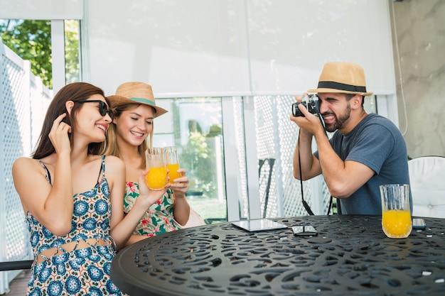 Portret van drie reizigersvrienden die wat tijd doorbrengen en wat foto's maken in het hotel. reis- en levensstijlconcept.