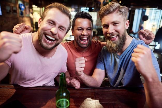Portret van drie schreeuwende mannen in de kroeg