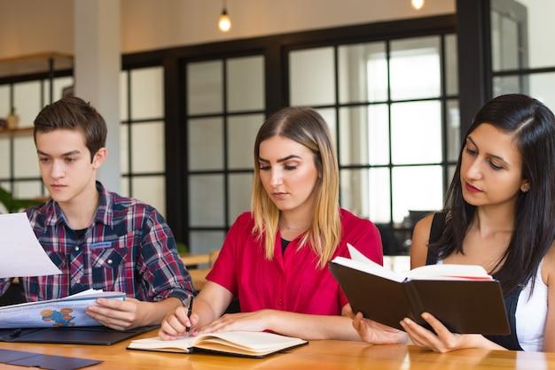 Portret van drie serieuze studenten studeren in de bibliotheek