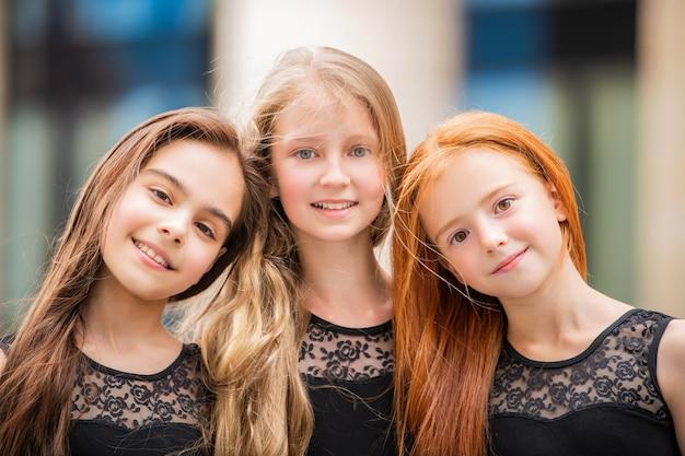 Portret van drie tienermeisjes met losse haren, blond, roodharige en brunette zomer op straat. vloses ontwikkelen zich in de wind.