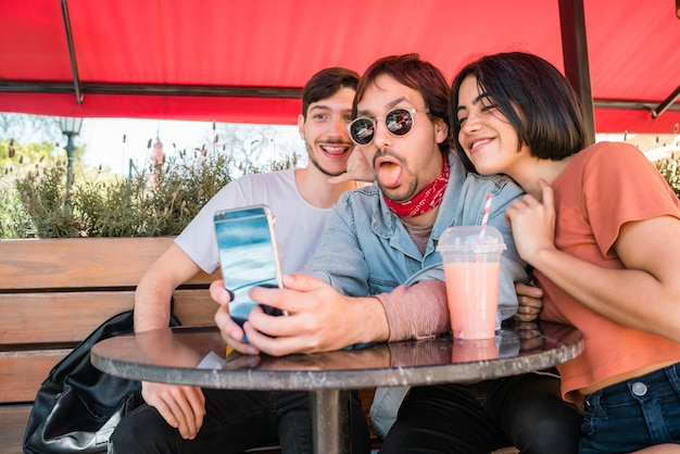 Portret van drie vrienden die goede tijd samen doorbrengen en een selfie met mobiele telefoon nemen bij coffeeshop. levensstijl en vriendschapsconcept.