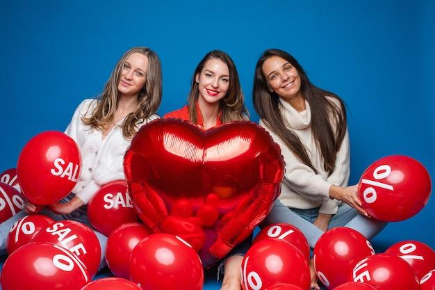 Portret van drie vrij lachende vriendinnen in casual kleding zitten met rode lucht ballonnen met verkoop- en procentteken