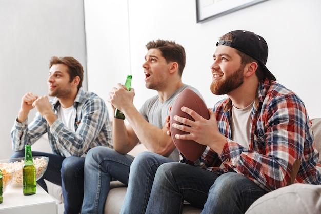 Portret van drie vrolijke jonge mannen kijken naar amerikaans voetbal zittend thuis met bier en snacks binnenshuis