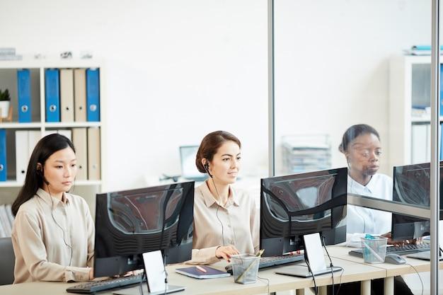 Portret van drie vrouwelijke exploitanten die in rij zitten en computers in call centrebureau gebruiken