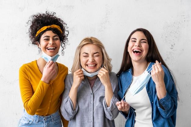 Portret van drie vrouwen met medische maskers lachen
