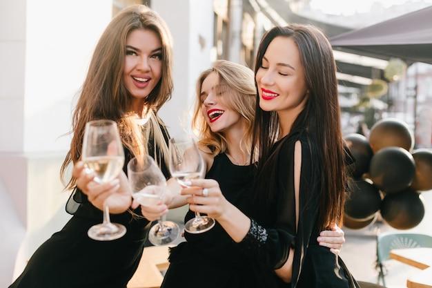 Portret van drie zusters in zwarte uitrusting die belangrijke gebeurtenis met champagne vieren
