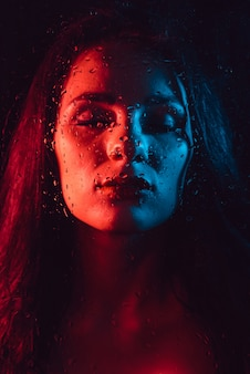 Portret van droevig jong meisje met rode blauwe verlichting achter glas met regendruppels