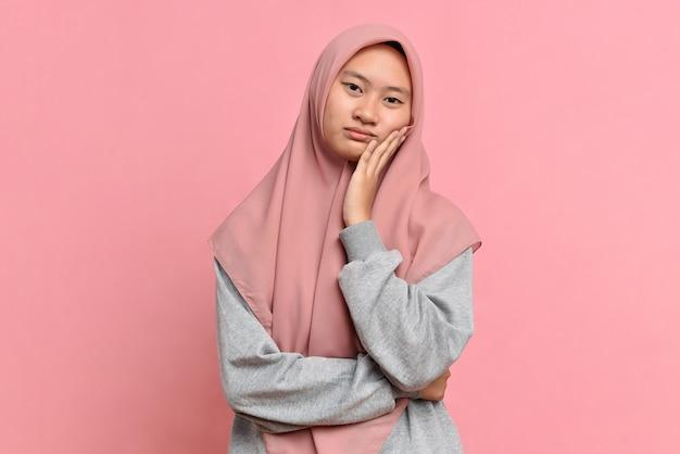 Portret van droevige aziatische moslimvrouw tegen roze achtergrond. verdriet hopeloos