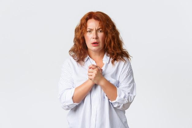 Portret van droevige en bezorgde roodharige vrouw van middelbare leeftijd drukt medeleven uit
