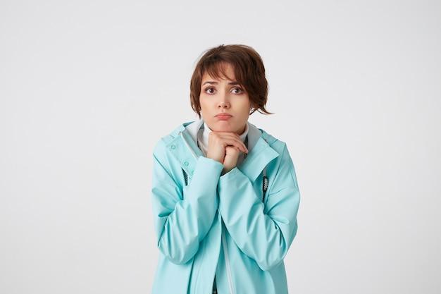 Portret van droevige jonge aardige dame in blauwe regenjas, met gebalde handen, ronduit kijkend naar de camera, staat over witte muur.