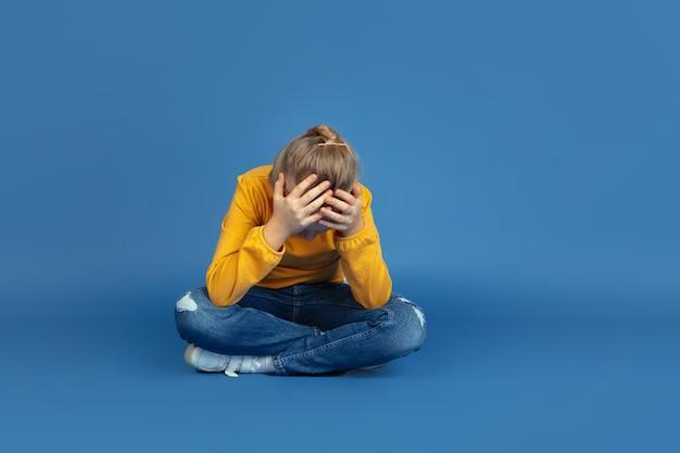 Portret van droevige meisjeszitting die op blauwe achtergrond wordt geïsoleerd.