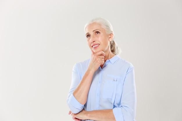 Portret van dromen van vrolijke oude dame, haar kin aanraken, opzij kijken