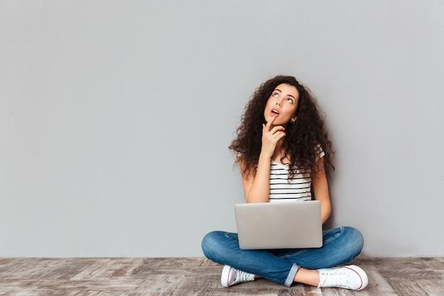 Portret van dromend wijfje in vrijetijdskleding die met benen zitten die op de vloer met gezicht worden gekruist dat omhoog in zilveren computer over grijze muur werkt