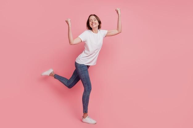 Portret van dromerige geïnspireerde kampioensdame steekt vuisten op, verbaasde stemming op roze achtergrond