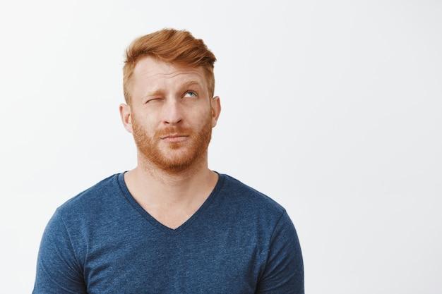 Portret van dromerige schattige volwassen roodharige man met baard, kijkend met één oog dicht, wenkbrauwen optillen, denken of een idee verzinnen, iets over grijze muur voorstellend