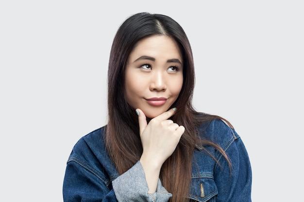Portret van dromerige smiley mooie brunette aziatische jonge vrouw in casual blauw spijkerjasje met make-up die haar kin aanraakt en nadenkt. indoor studio opname, geïsoleerd op lichtgrijze achtergrond.