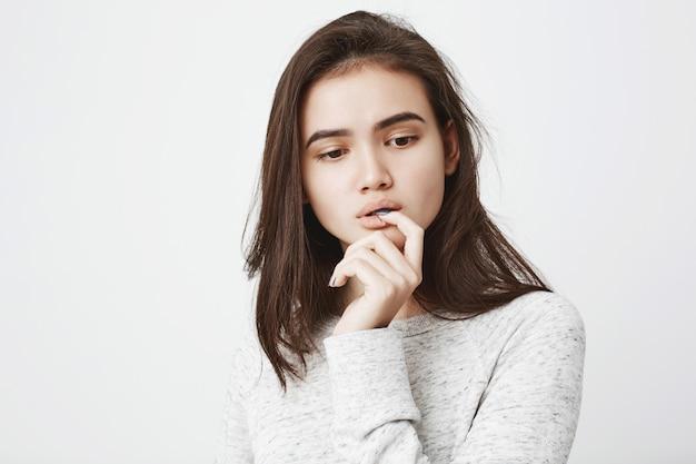 Portret van dromerige tedere vrouw met doordachte expressie, hand in de buurt van mond houden terwijl vinger bijten en naar beneden te kijken