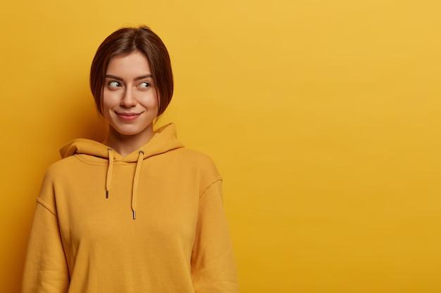 Portret van dromerige tevreden jonge europese vrouw kijkt opzij op lege ruimte, heeft een aangename uitstraling, draagt een hoodie, poseert tegen een gele muur, lege ruimte, heeft een intrigerend plan in gedachten.