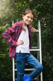 Portret van een 10-jarig meisje dat zich voordeed op een trapladder in de tuin