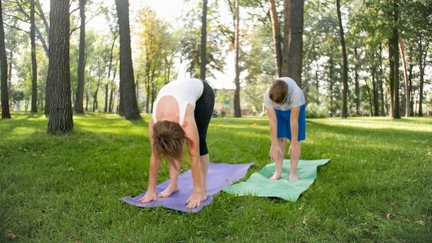 Portret van een 12-jarige jongen die yogaoefening doet met zijn moeder in het park. familie mediteren en strekken in het bos