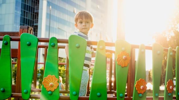 Portret van een 3 jaar oude kleine jongen die loopt en kruipt op een hoge houten brug op de kinderspeelplaats in het park. kinderen spelen en plezier hebben op de speelplaats