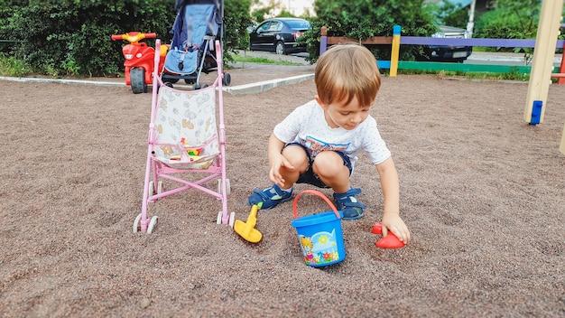 Portret van een 3 jaar oude peuterjongen die op de speelplaats zit en zand graaft met plastic schop en emmer