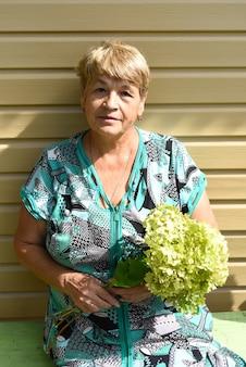 Portret van een 70-jarige vrouw die op een bank zit en een boeket hortensia vasthoudt