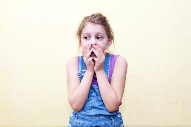 Portret van een 8-jarig meisje op gele muur, bang voor haar mond met haar handen